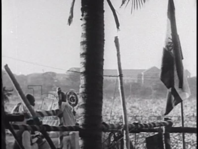 Gandhi surrounded by followers and on a balcony, India, 1930s