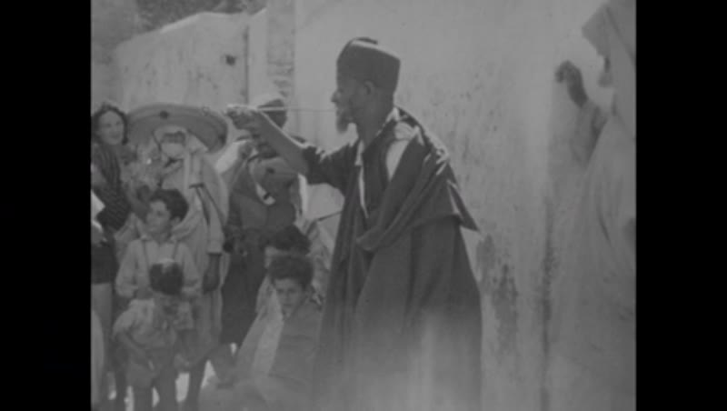 Sword swallower performs on the street in town or city in North Africa, possibly Algeria or Morocco, 1933