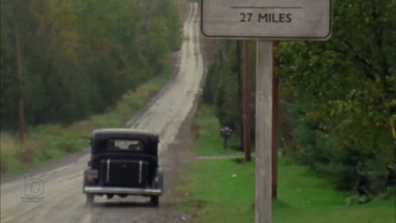 1930s automobile drives down country road in the rain