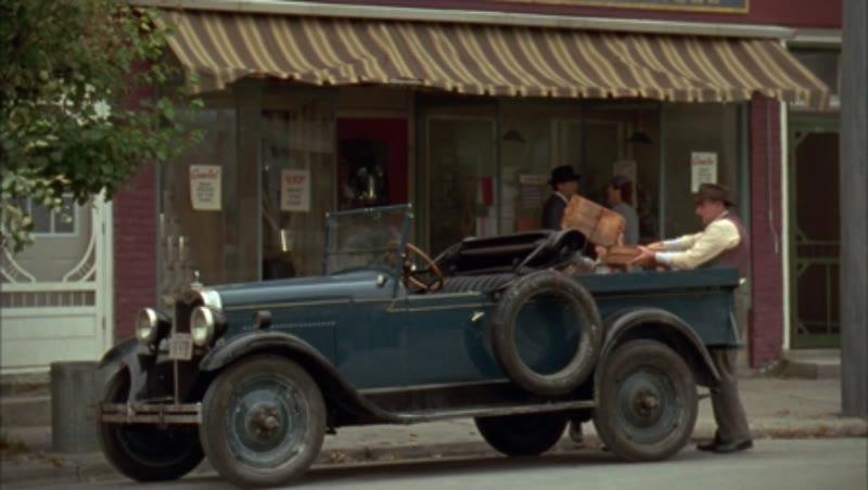 Man loading automobile outside storefront, 1930s - reenactment