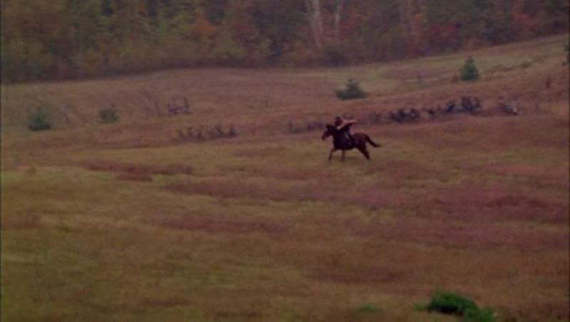 Man on horseback riding through the countryside, 1908 - reenactment. Clip 7