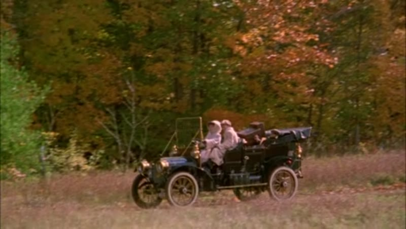 Man and woman driving in a car in the countryside, 1908 - reenactment