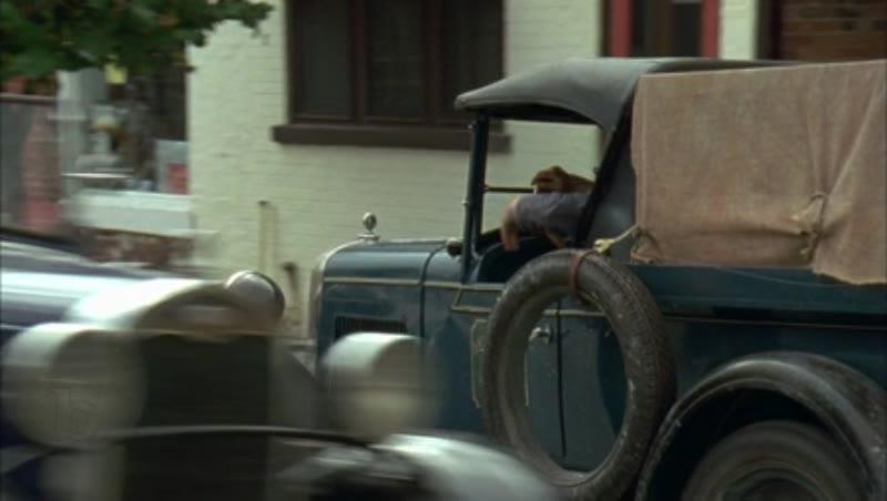 Car driving through town, 1930s - reenactment