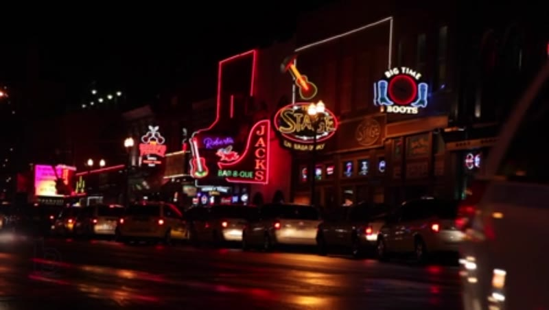 Static shot of cars and neon lights along Main Street in Nashville, Tennessee at night