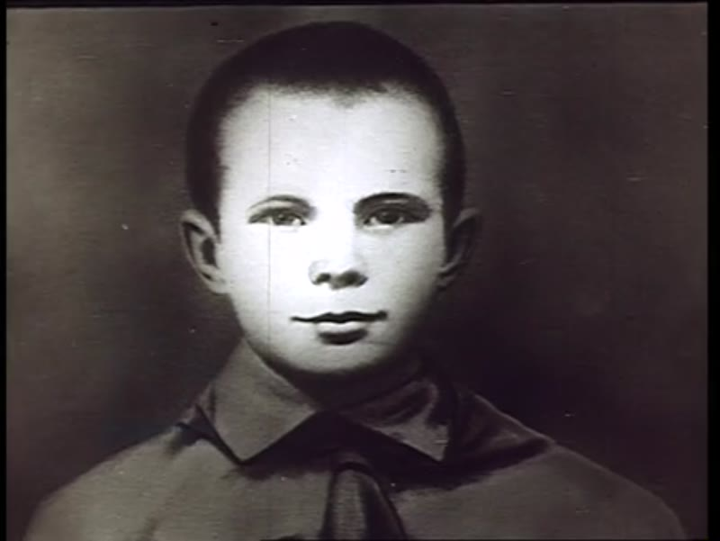 Yuri Gagarin talks about his childhood to the camera in 1960s. Shot of traditional Russian izba home with children outside.