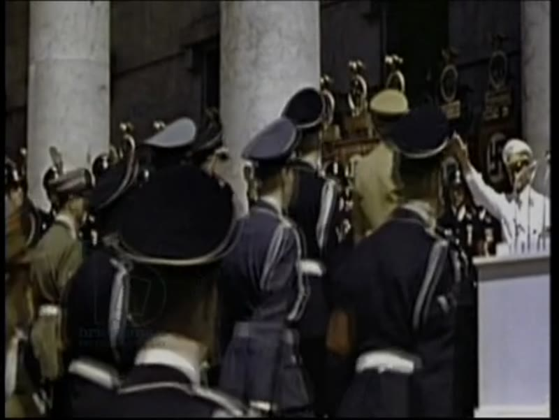 Hitler at an event, with SS officers including Himmler in uniform. Colour footage.
