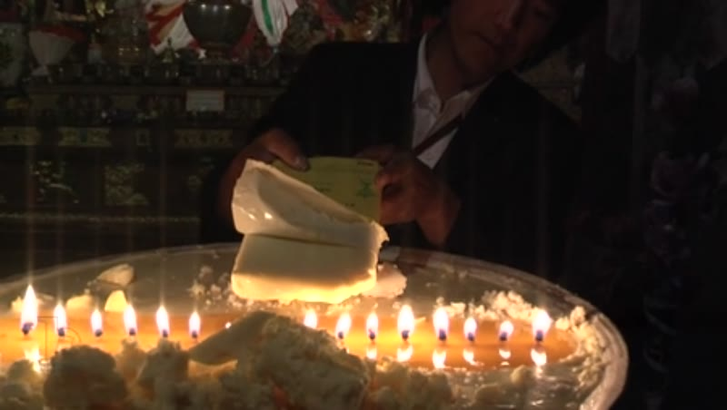 Man offering butter to lamps, Samye Monastery, Tibet