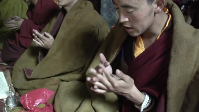 Monks praying with hand gestures inside the main Assembly hall, Sakya Monastery, Tibet