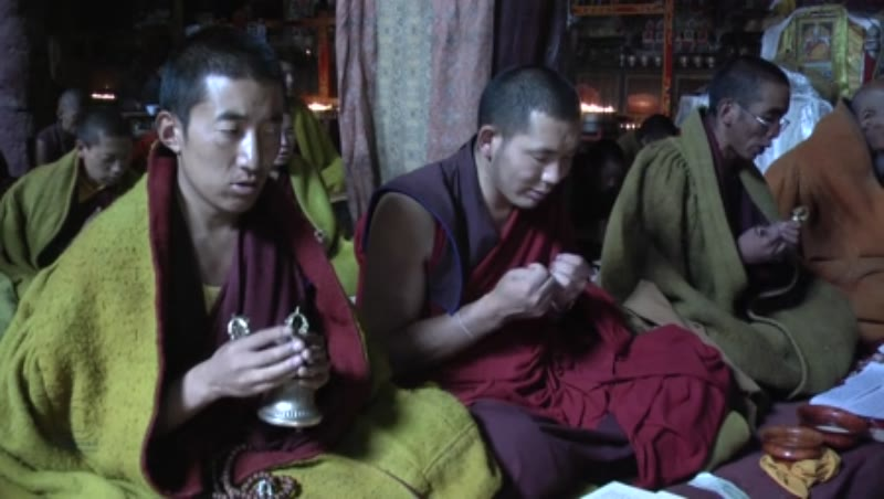 Monks praying with vajra and bells inside the main Assembly hall, Sakya Monastery, Tibet