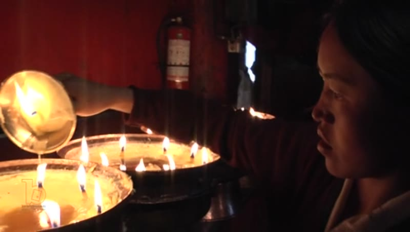 Woman offering butter oil to lamps, Ramoche Temple, Lhasa, Tibet