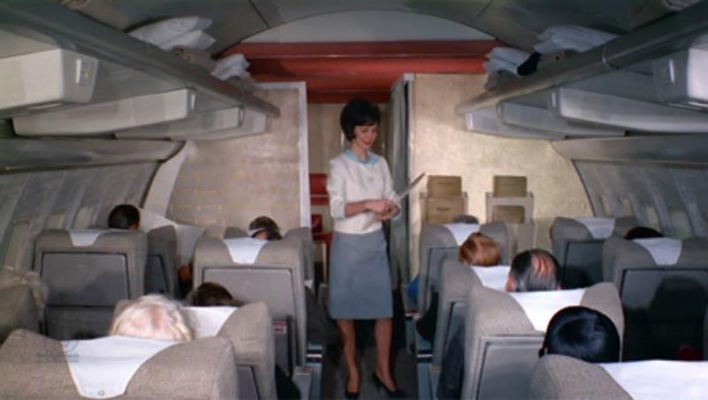 Cabin Stewardess passes out menu's on plane