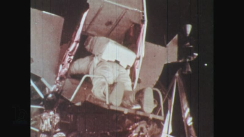 1970s man exits lunar module door and steps onto the moon surface