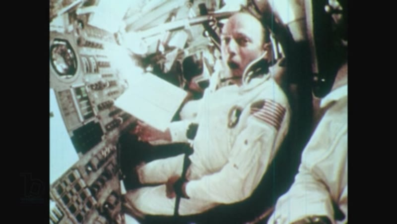 1970s men float around cockpit and read clipboard in command module