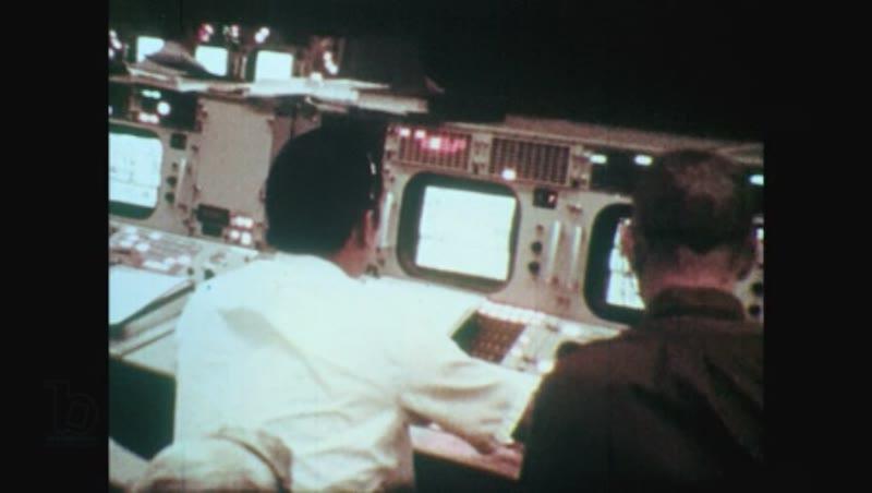 1970s man reads clipboard in cockpit of command module in zero gravity