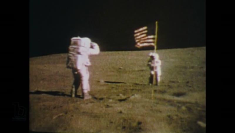 United States, 1960s: Men on moon salute USA flag