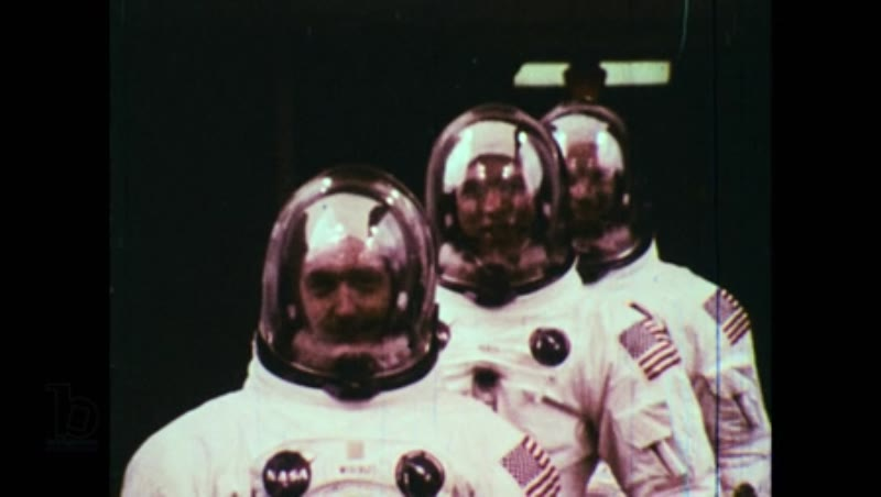 United States, 1960s: Astronauts in space suits walk out of building and wave