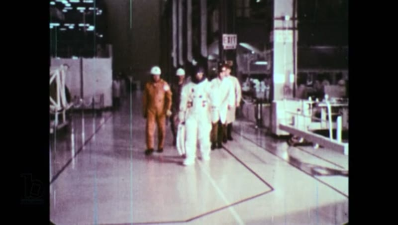 United States, 1960s: Nasa astronaut walks through building surrounded by technical team