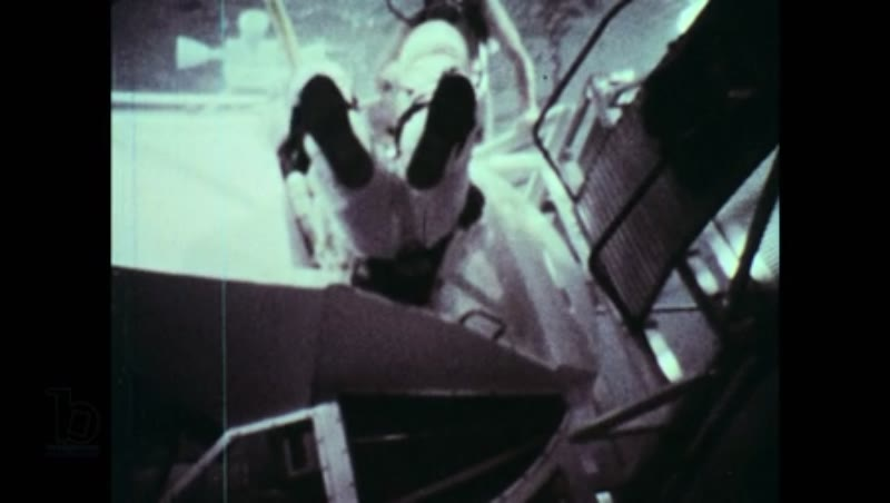 United States, 1960s: NASA astronaut enters swimming pool in space suit, through hatch