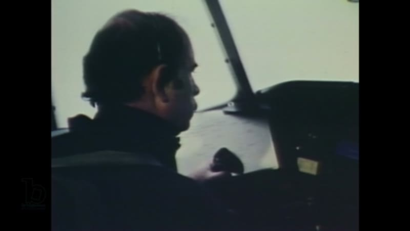 1980s: A man operates the controls of an airplane