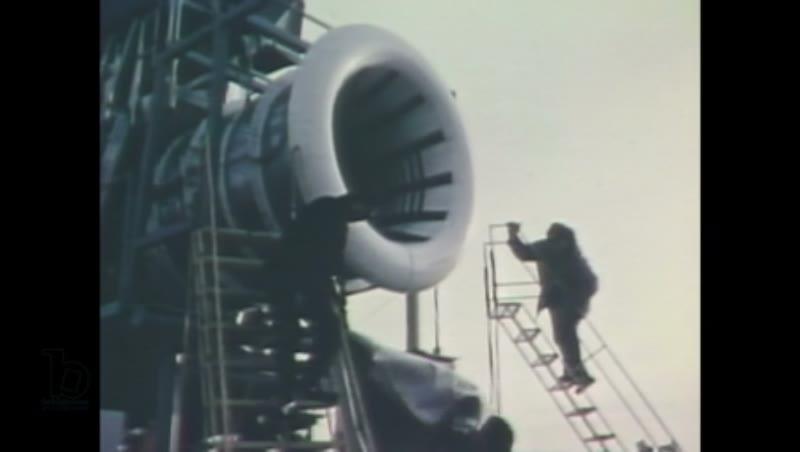 1980s: A man sets up microphones on poles outside a NASA facility