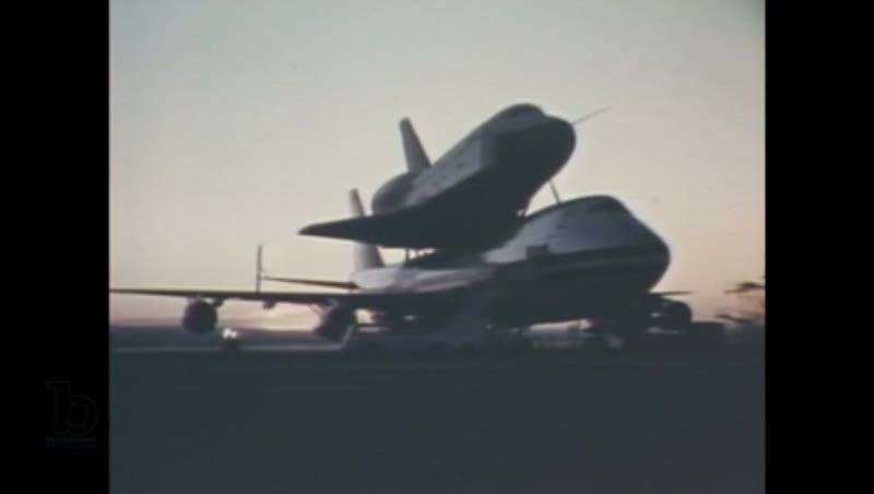 1980s: Space shuttle Enterprise, mounted on a Boeing 747, parked at a NASA facility at sunset