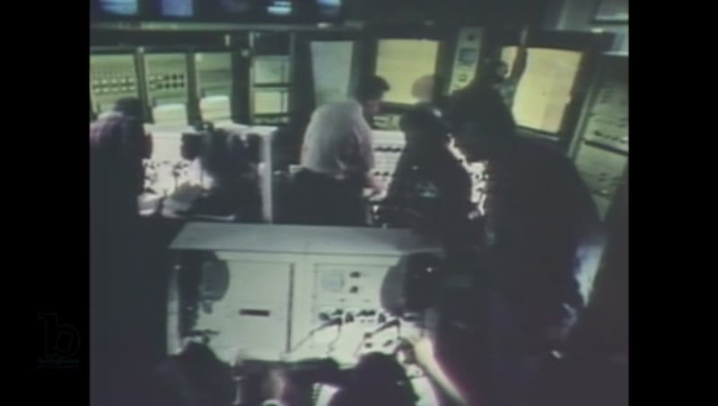 1980s: Men talk into headsets and radios in a busy control room