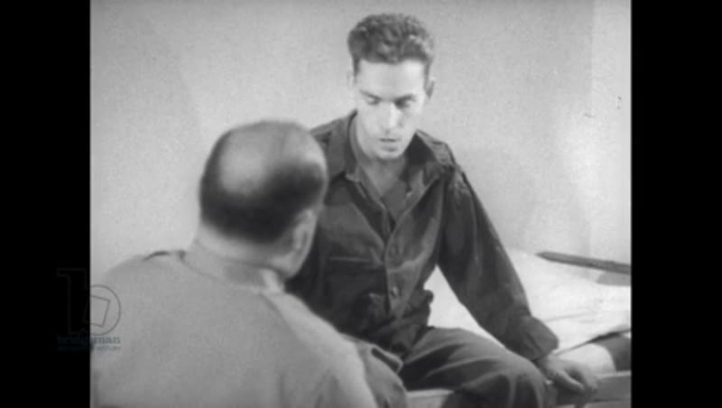 1940s: Patient sits on bed, consults with seated hospital worker, gestures to chest and points to back, legs spasm.