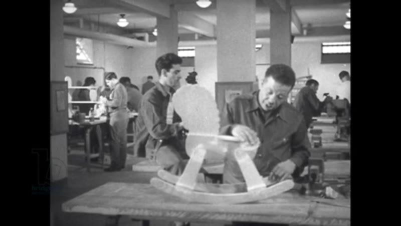 1940s: Man fixes machine part.