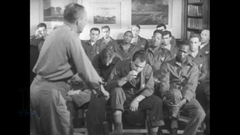 1940s: Male patients in uniform, seated in rows, listen to therapist.