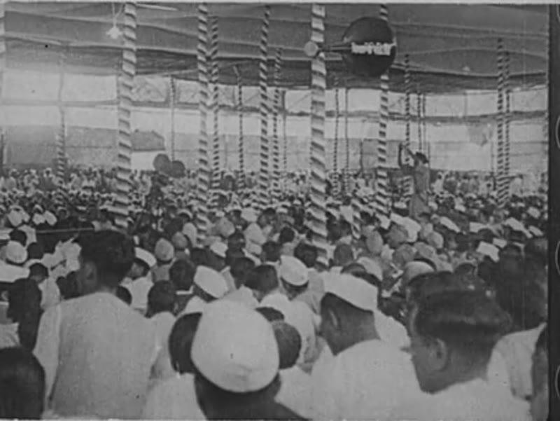 India, c.1940: A crowd of Indian men, many wearing Gandhi topis and mundus, sit in a large hall. Women in saaris serve men drinks.