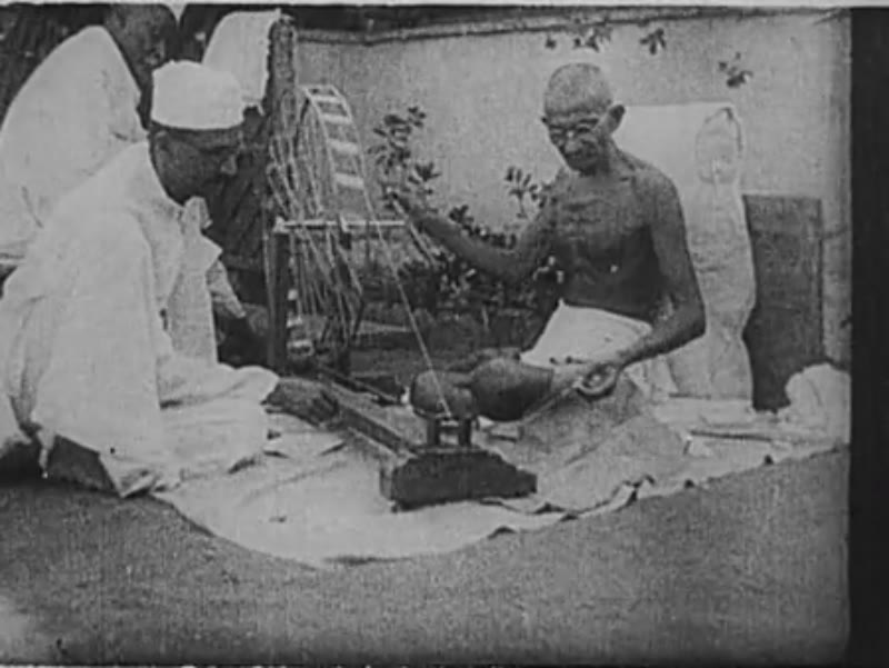 India, circa late 1920s: Gandhi spins yarn, assisted by a man in a topi and mundu