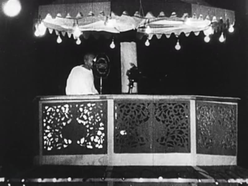 India, c.1930: Gandhi stands on a canopied stage and speaks into a microphone.