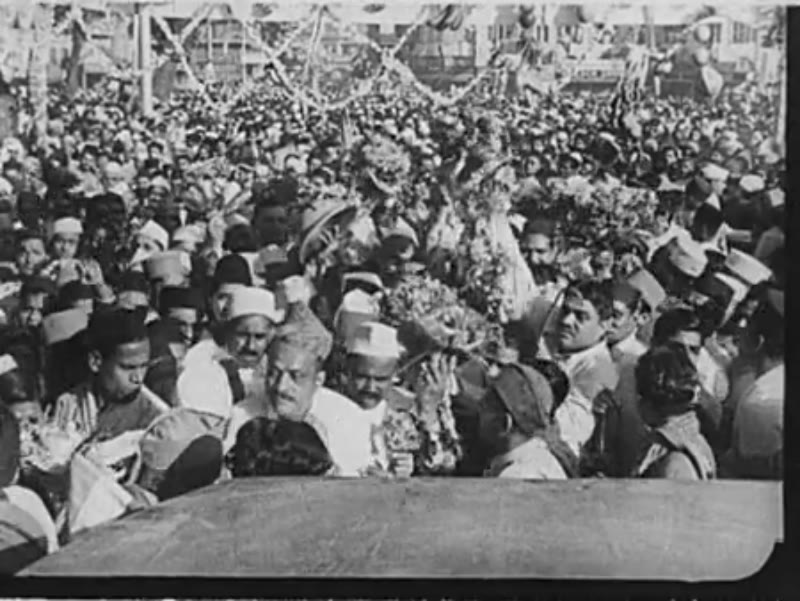 India, c.1930: A large crowd greets Gandhi as he steps out of a car and acknowledges its members.