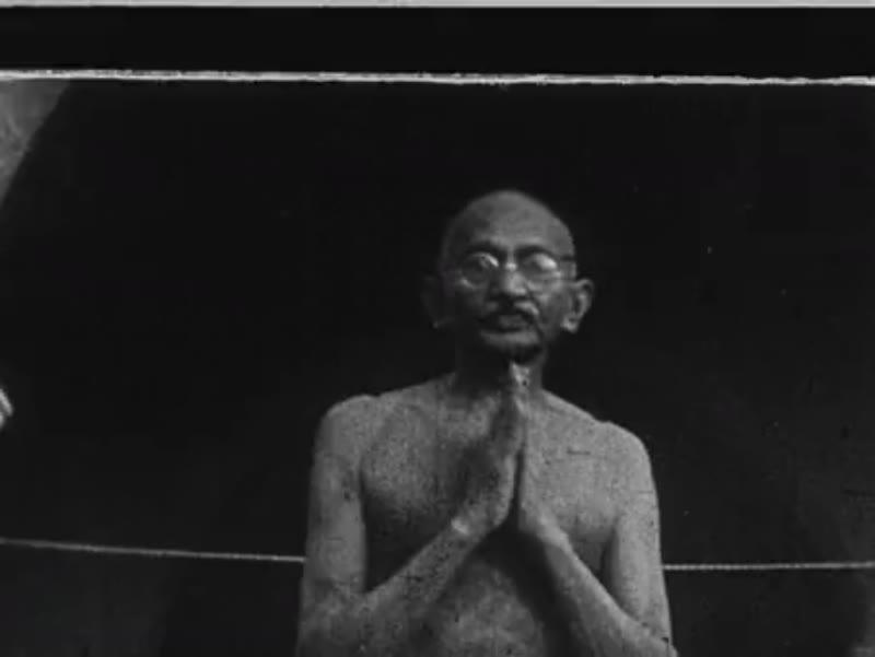 India, c.1930: Gandhi speaks to smiling reporters