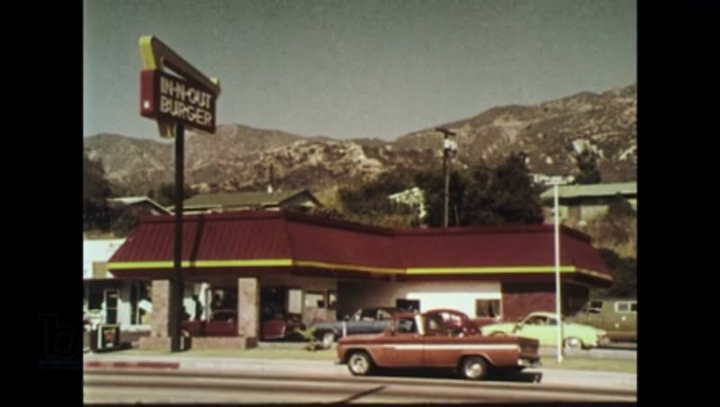 UNITED STATES 1970s - A burger is prepared by grilling the patty and heating the buns.