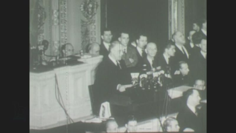 1940s: Franklin D. Roosevelt speaks at conference podium, men stand listening