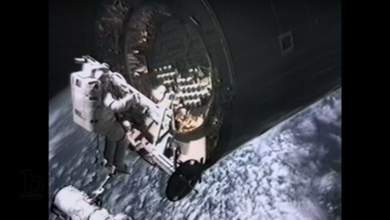 America, c.1990s: Medium close up: Astronaut in space receives telecom instruction while trying to attach capture bar on satellite