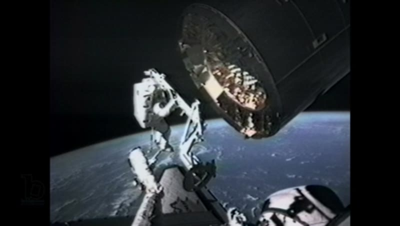 America, c.1990s: Medium shot: Astronaut in space receives telecom instruction while attaching capture bar on satellite