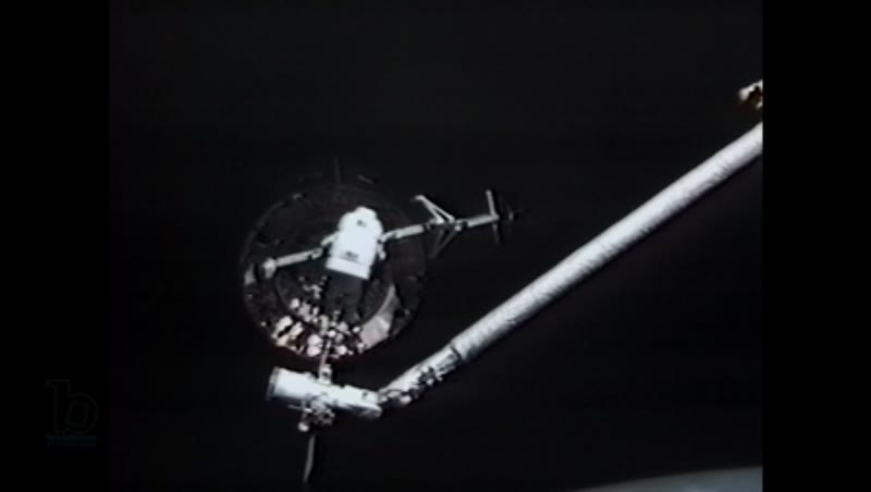 America, c.1990s: Long shot: Astronaut in space receives telecom instruction while trying to attach capture bar on satellite