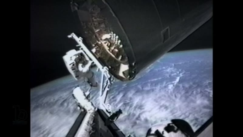 America, c.1990s: Robotic arm controllers maneuver astronaut, on STS-49 mission, toward a rotating satellite