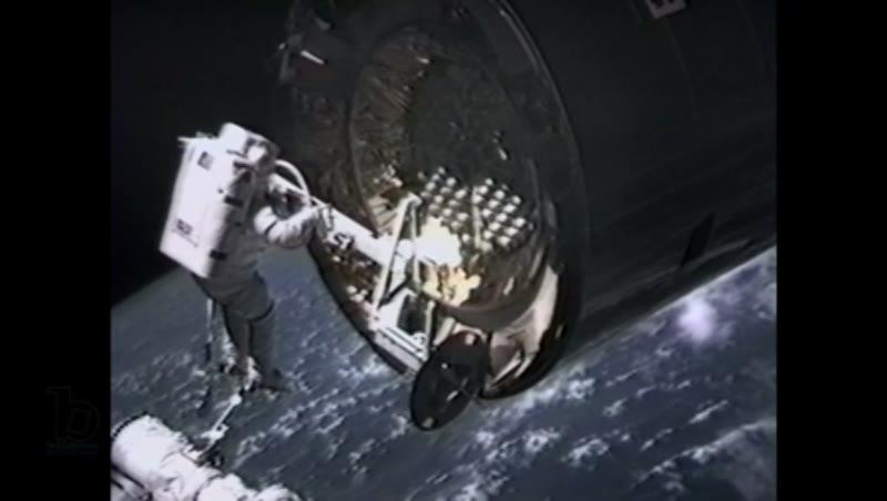America, c.1990s: Medium shot: Robotic arm controllers maneuver astronaut, on STS-49 mission, toward a rotating satellite