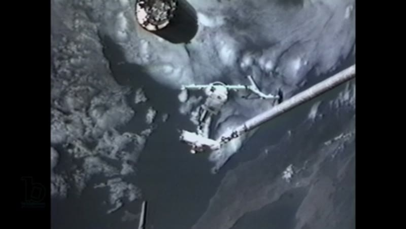America, c.1990s: Long shot: Astronaut, attached to a robotic arm and holding a capture bar, moves away from a satellite in orbit