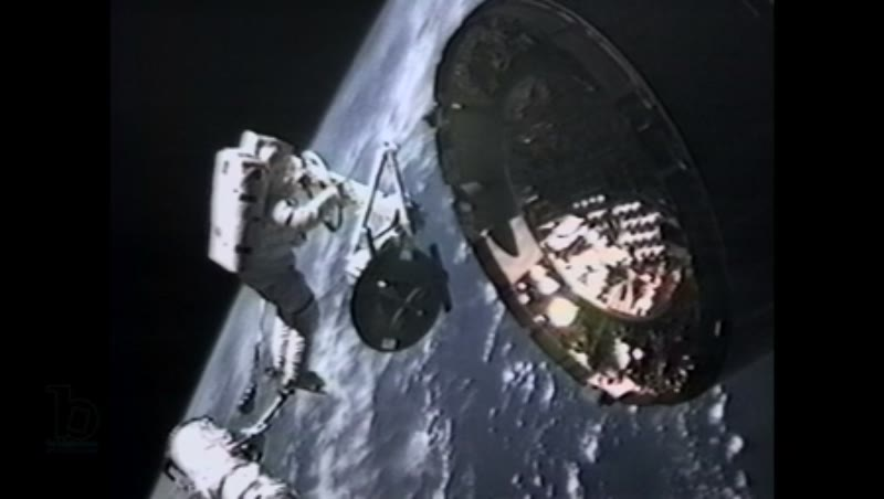 America, c.1990s: Medium close up: Astronaut in space receives telecom instruction while installing capture bar on satellite