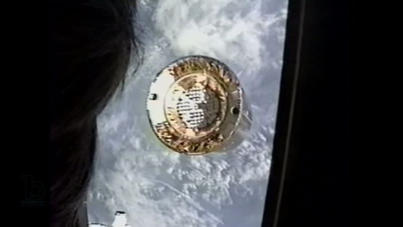 America, c.1990s: Video from inside space shuttle Endeavour of satellite in orbit