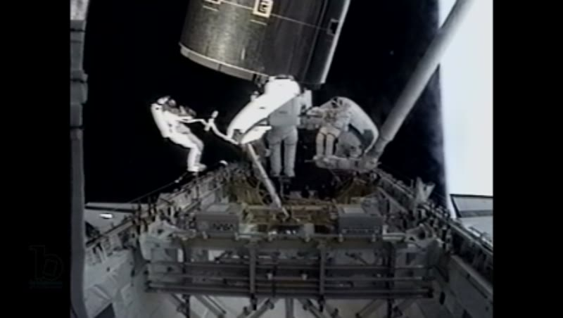 America, c.1990s: Three astronauts, attached to robotic arms, receive telecom instructions while working with satellite near exterior of space shuttle Endeavour