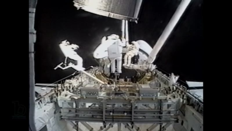 America, c.1990s: Three astronauts on exterior of space shuttle Endeavour as Intelsat VI satellite slowly moves into frame from top of frame