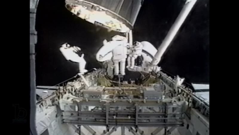 America, c.1990s: Three astronauts on exterior of space shuttle Endeavour as Intelsat VI satellite hovers above them