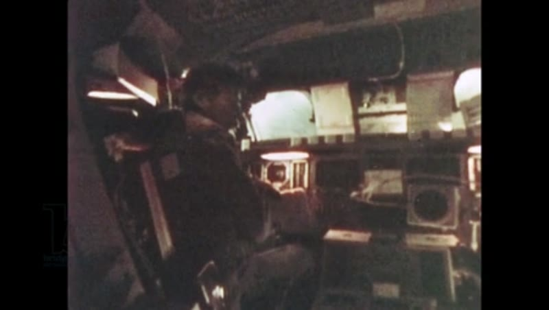 UNITED STATES: 1981: Seated astronaut working inside cabin of space shuttle.