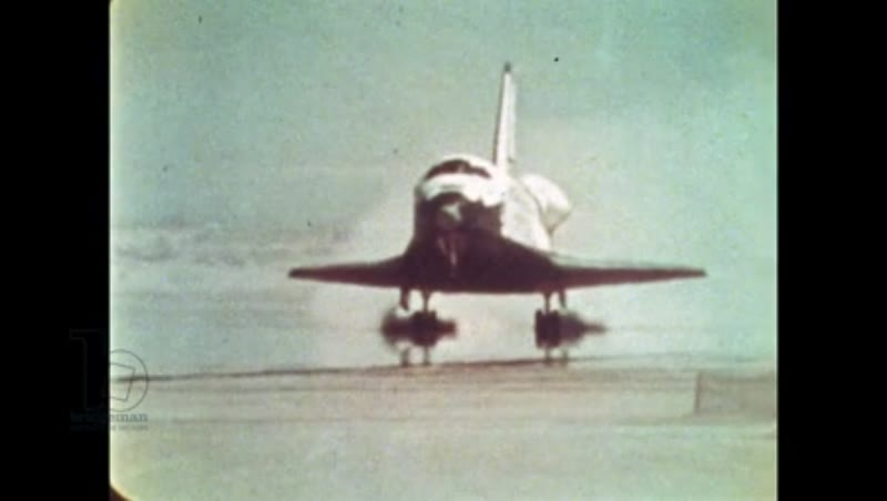 UNITED STATES: 1981: Close up of front of space shuttle as it lands on sandy runway.