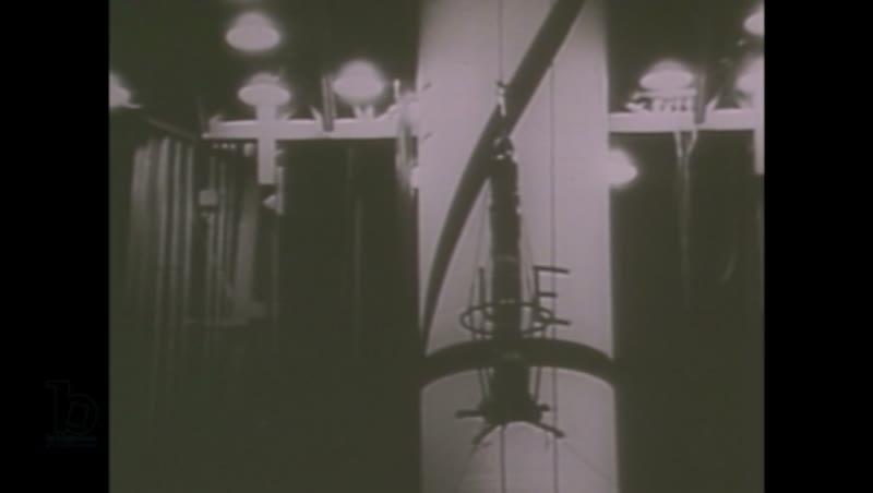 1980s: Men in uniforms sit around model rocket, talking